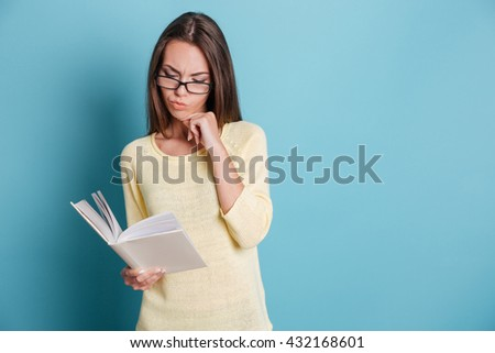 Beautiful pensive young girl in eyeglasses reading book over blue background - stock photo