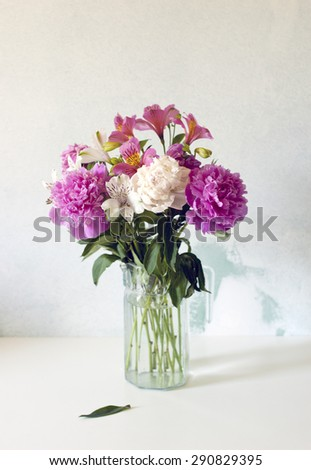 Beautiful peonies bouquet in glass vase