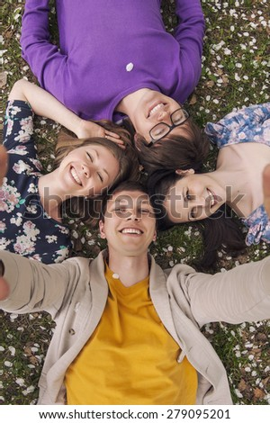 Beautiful people friends lying on the grass smiling happily - stock photo