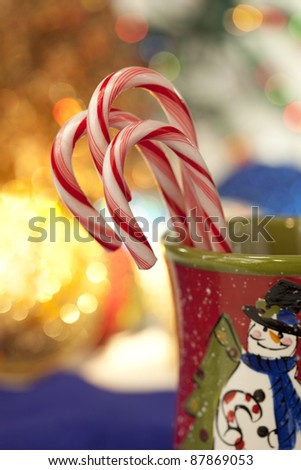 Beautiful peppermint candy canes in colorful Christmas mug with holiday lights in background - stock photo