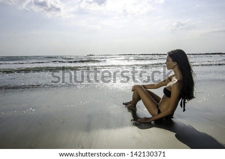 Beautiful perfect brunette woman enjoying summer on the beach and sea waves, girl looking at the beautiful scene - stock photo