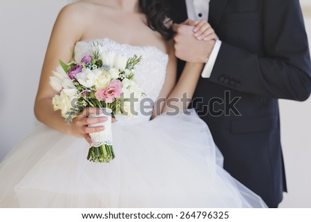 Beautiful, perfect couple posing on their wedding day. Close up hands and wedding bouquet - stock photo