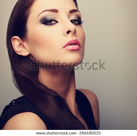 Beautiful perfect makeup woman looking with smoky eyes. Color closeup portrait - stock photo