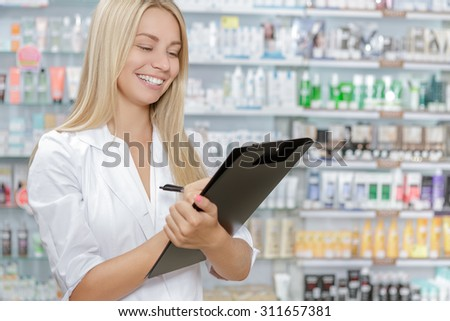 Beautiful pharmacist accounting the product in drugstore