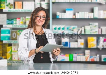 Beautiful Pharmacist with Digital Tablet in a Drugstore - stock photo