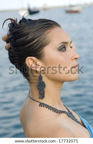 Beautiful photo of an attractive woman holding her hair up with her back showing - stock photo