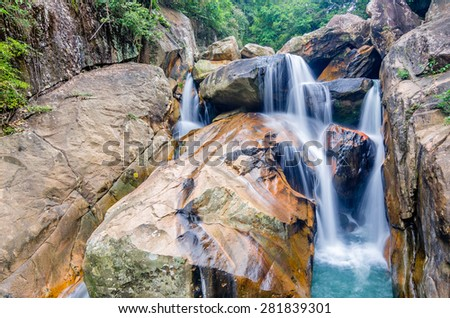 Beautiful photo of waterfalls with soft flowing water and large colored rocks. Green wild jungles on background.