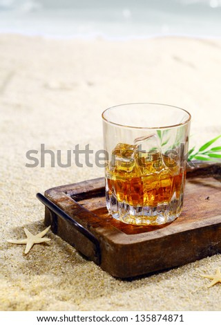 Beautiful photograph of a glass of scotch with ice cubes in a classy wooden tray on the beach. Look at my portfolio for whole series of cocktails. - stock photo