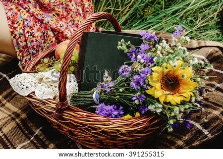 beautiful picnic wicker basket with colorful bouquet fruits and books on tweed plaid, happy bride and stylish groom legs - stock photo