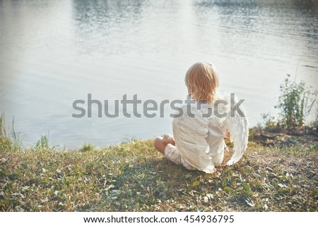 beautiful picture - angel valentine boy sitting on beach on sunset