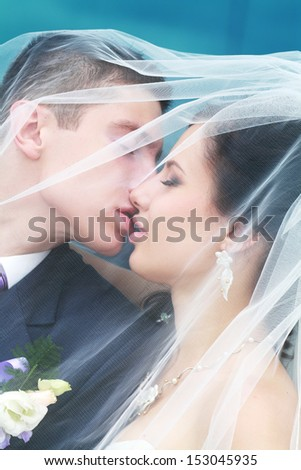 Beautiful picture of a nice young married couple kissing on a street - stock photo