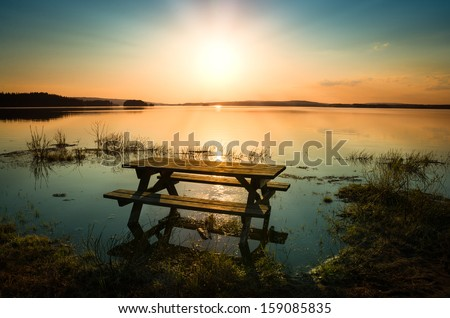 beautiful picture of a table with bench by a lake with the sun and sunbeams in the sky - stock photo