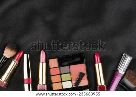 Beautiful picture of cosmetic  on black satin, with space for your text - stock photo