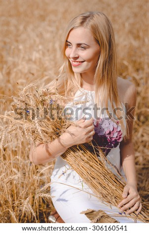 Beautiful picture of smiling blond lady with long blond hair holding sheaf of wheat sticks sitting on field looking away.