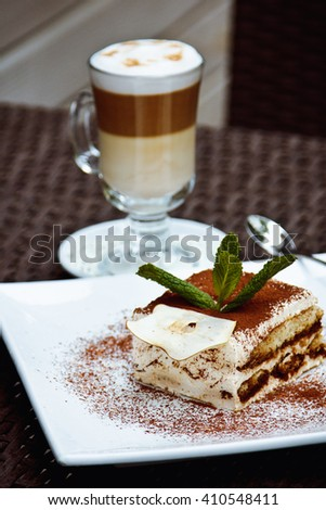 Beautiful piece of delicious tiramisu with fresh mint and chocolate chip  and latte in a cafe. - stock photo