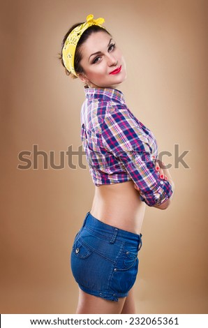 Beautiful pin-up girl. A woman dressed in a plaid shirt and on her head tied bandana - stock photo