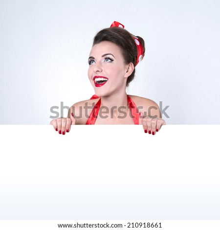 Beautiful pin-up girl holding empty white board - stock photo
