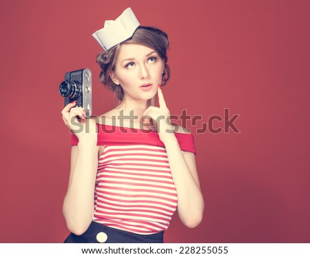 Beautiful pin-up girl holding in his hand a vintage camera - stock photo