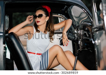 Beautiful pin-up girl inside vintage car - stock photo