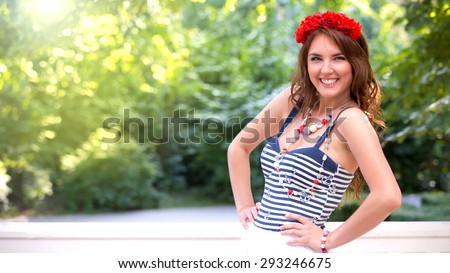 Beautiful pin-up girl with flowers in hair, posing in a green park. Soft focus