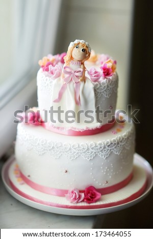 Beautiful pink birthday cake with little doll figurine on top - stock photo