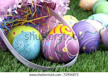 Beautiful pink easter basket with  decorated eggs in green grass - stock photo