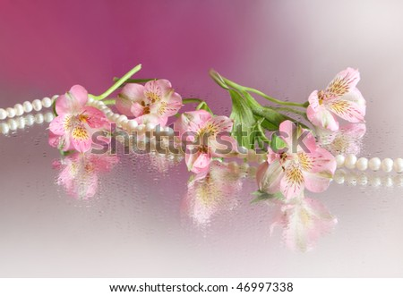 Beautiful pink flower and pearl necklace - stock photo