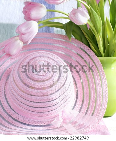 beautiful pink hat with pink tulips in green vase - stock photo