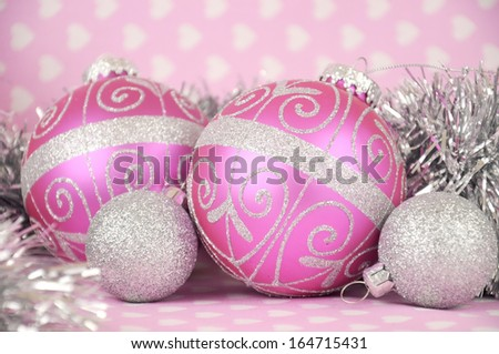 Beautiful pink Merry Christmas bauble decoration ornaments close up against a pink heart and polka dot ribbon background. Selective focus. - stock photo
