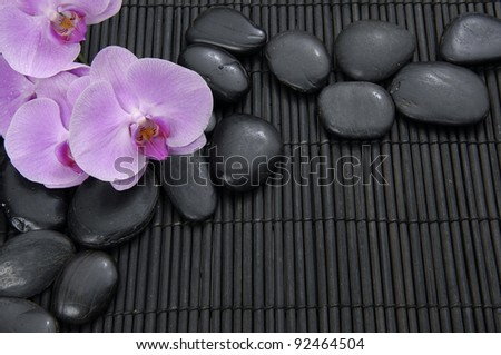Beautiful pink orchid with stones on bamboo mat - stock photo