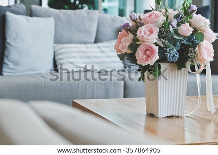 Beautiful Pink rose in vase on table in living room. - stock photo