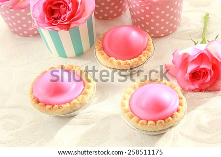 Beautiful pink roses and fresh pink cakes on the table - stock photo