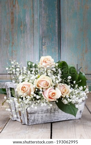 Beautiful pink roses and gypsophila paniculata (Baby's-breath flowers) in wooden box. Wedding decor idea - stock photo