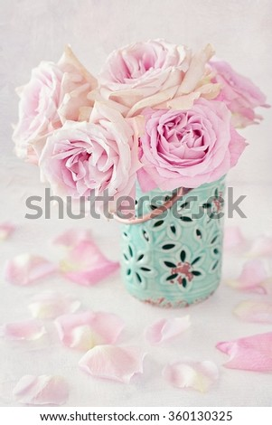 Beautiful pink roses in a blue ceramic vase on a light background.  - stock photo