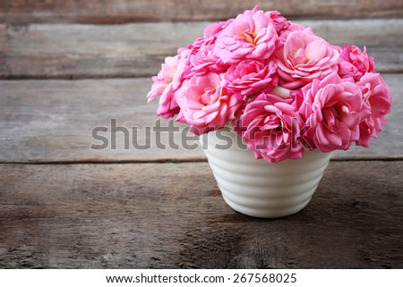 Beautiful pink roses in pot on wooden background - stock photo