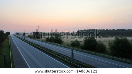 beautiful pink sky just before sunrise and fog lying over the highway and around fields - stock photo