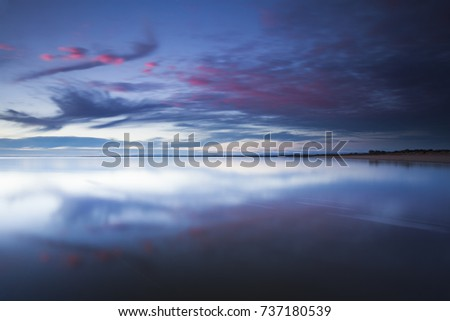 Beautiful pink twilight clouds reflecting on a calm glassy bay