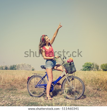 Beautiful pinup girl having fun cycling in fields under bright blue summer sky and pointing up on summer outdoors copy space background