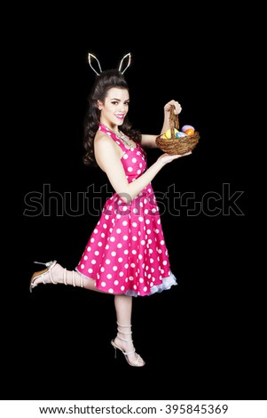 Beautiful pinup girl with rhinestone bunny ears and a basket of eggs.  Black background.