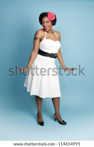 Beautiful pinup model wearing dress and hair flower - stock photo