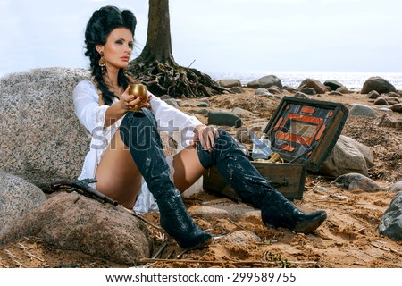 Beautiful pirate woman sitting near treasure chest on the beach with a golden goblet in her hand