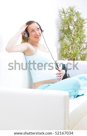 Beautiful piregnant woman sits on a sofa and listens to music - stock photo