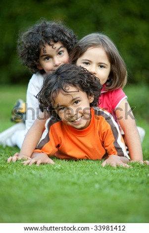 Beautiful playful kids lying on grass outdoors