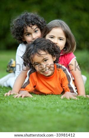 Beautiful playful kids lying on grass outdoors - stock photo