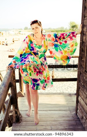 Beautiful plus size model is posing in colourful dress. - stock photo