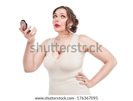 Beautiful plus size woman looking in the mirror  - stock photo
