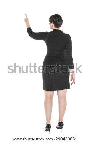 Beautiful plus size woman showing on something by finger isolated. Back pose  - stock photo