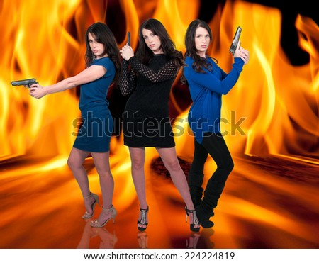Beautiful police detective women on the job with guns in a fire - stock photo