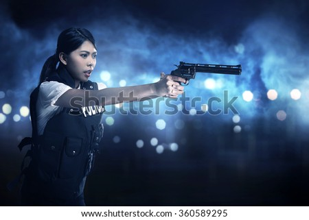 Beautiful police woman holding gun ready to fire