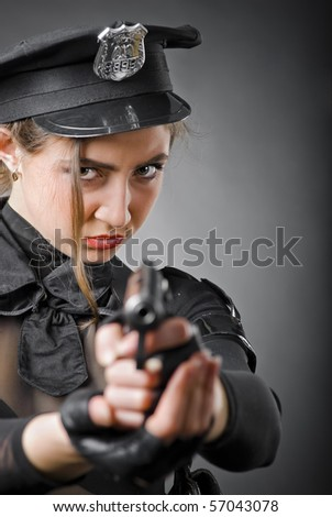 beautiful policewoman aiming a gun on a gray background - stock photo